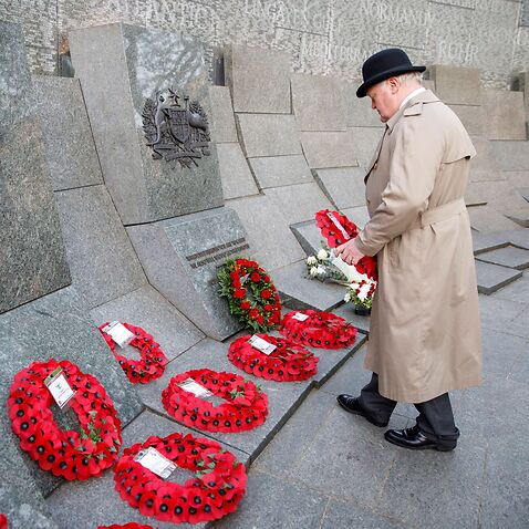 A member of the public lays a wreath during a Dawn Service at the Australian memorial, Wellington Arch, London, to commemorate Anzac Day.