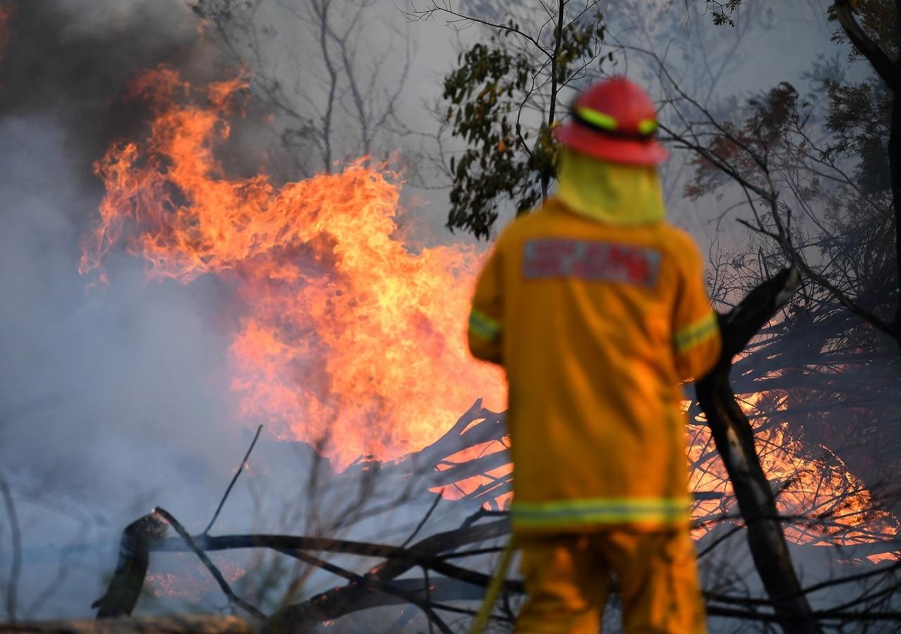 A firefighter defends a property in Torrington, near Glen Innes on Sunday.