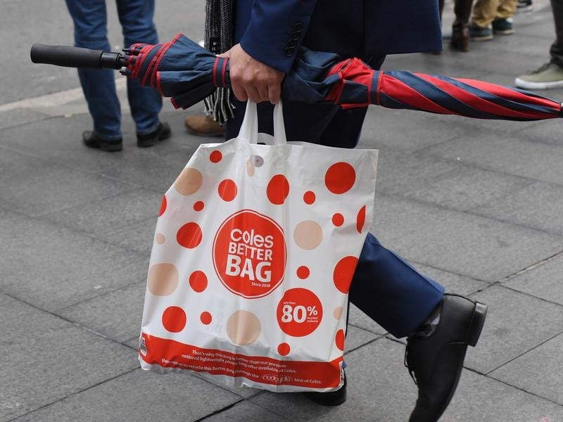 A shopper is seen carrying a reusable plastic bag from Coles.