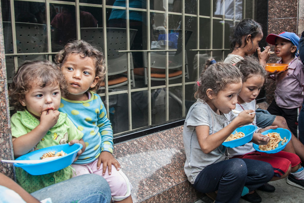 Venezuelan children heat food distributed from volunteers.