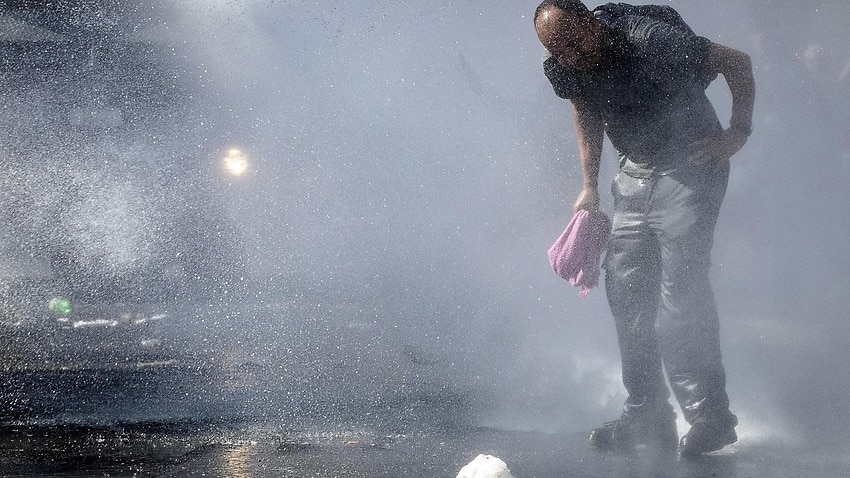 Italian law enforcement officers use water cannons to disperse about a hundred migrants protesting