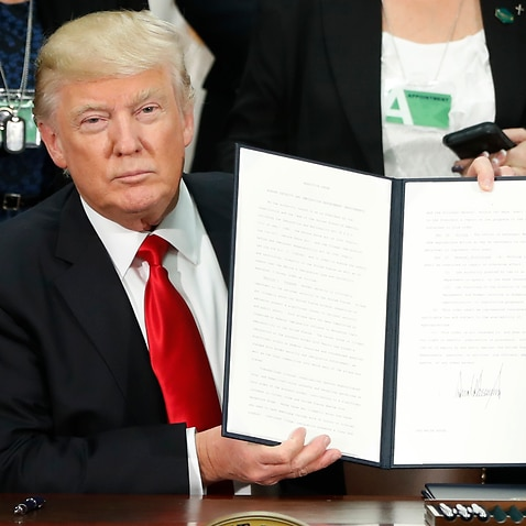President Donald Trump holds up an executive order for border security and immigration enforcement improvements.