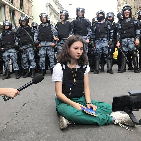 Olga sits cross-legged in front of riot police with the Russian constitution on her lap,