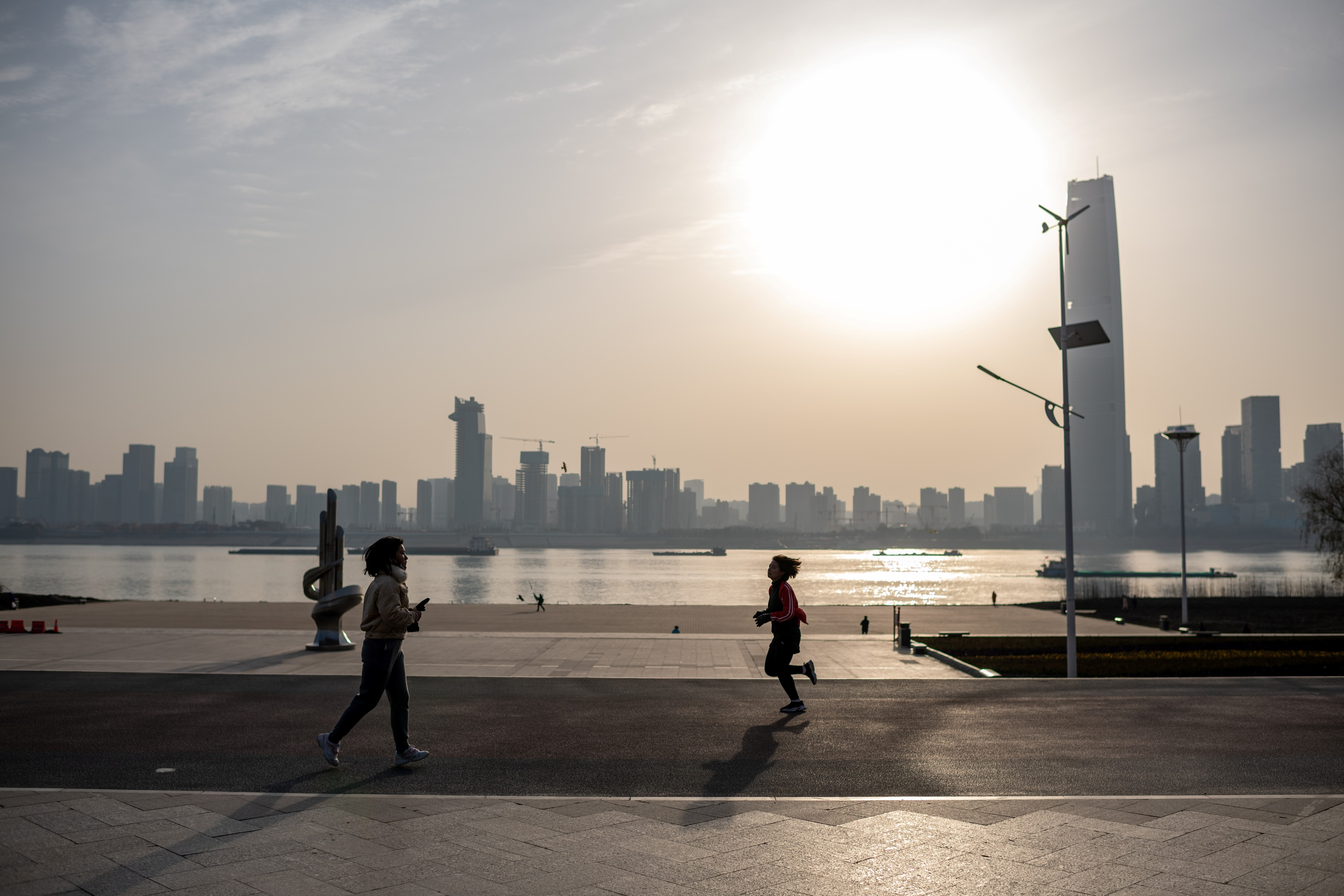 People run along the banks of the Yangtze River in Wuhan on 11 January, as the city marks the first anniversary of China confirming its first COVID-19 death.