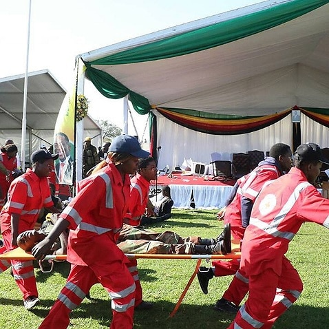 Members of the Zimbabwe Red Cross Society carry an injured member of the Zimbabwe National Army (ZNA), who was reportedly injured in the blast.