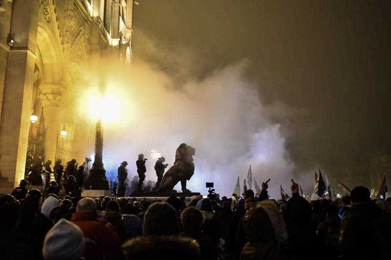 Protesters clash with police during a demonstration outside Budapest's parliament building, against amendments to the labour code