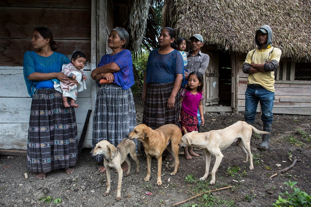 Members of the Caal Maquin family and neighbours stand in front of Claudia Maquin's house in Raxruha, Guatemala.