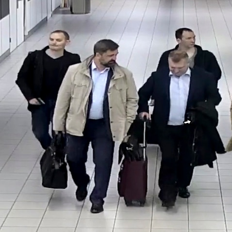 Four Russian officers of the GRU, are escorted to their flight after being expelled from the Netherlands in April