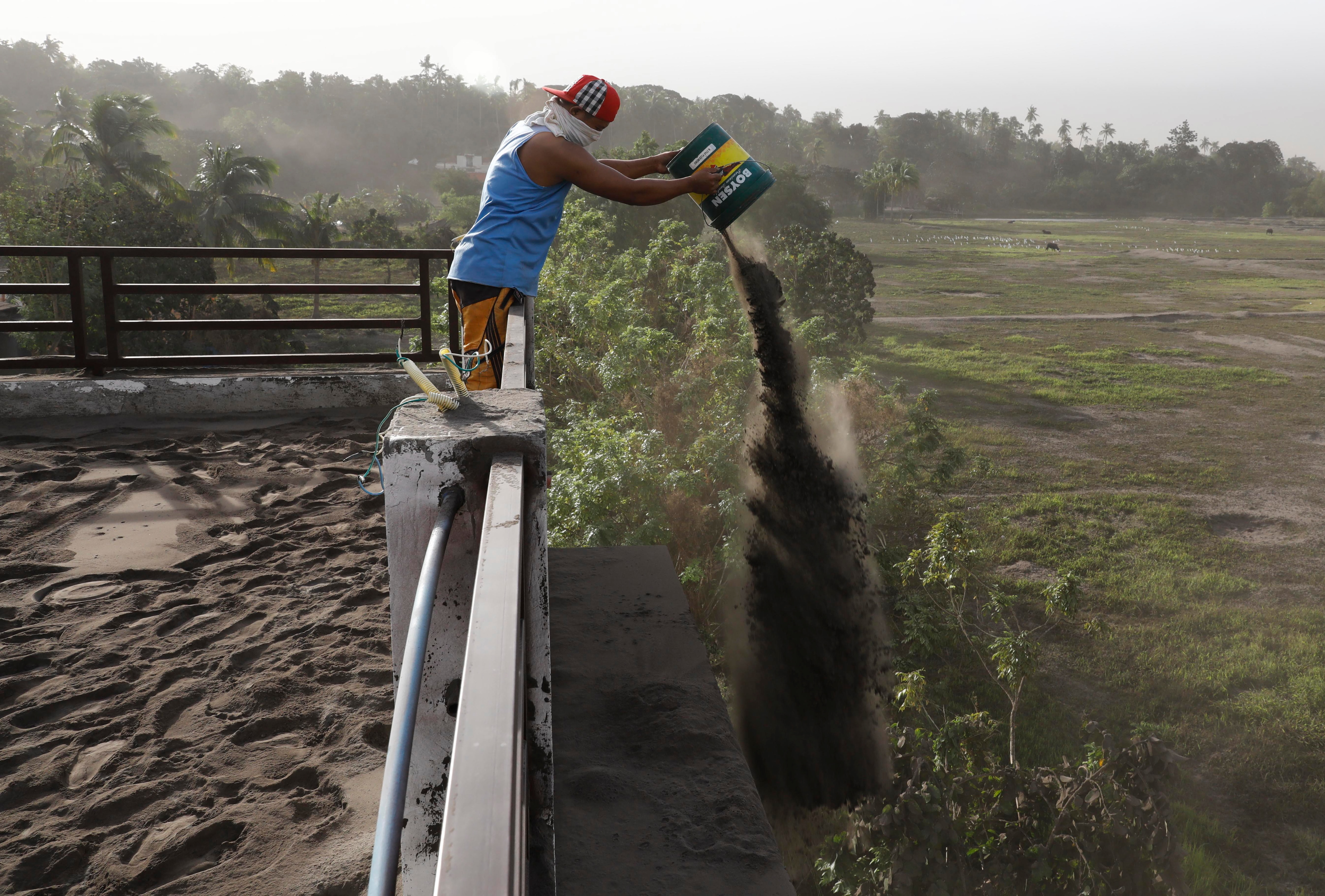 A man throws out ash deposits that accumulated on the roof of his home, a day after the eruption of Taal Volcano.