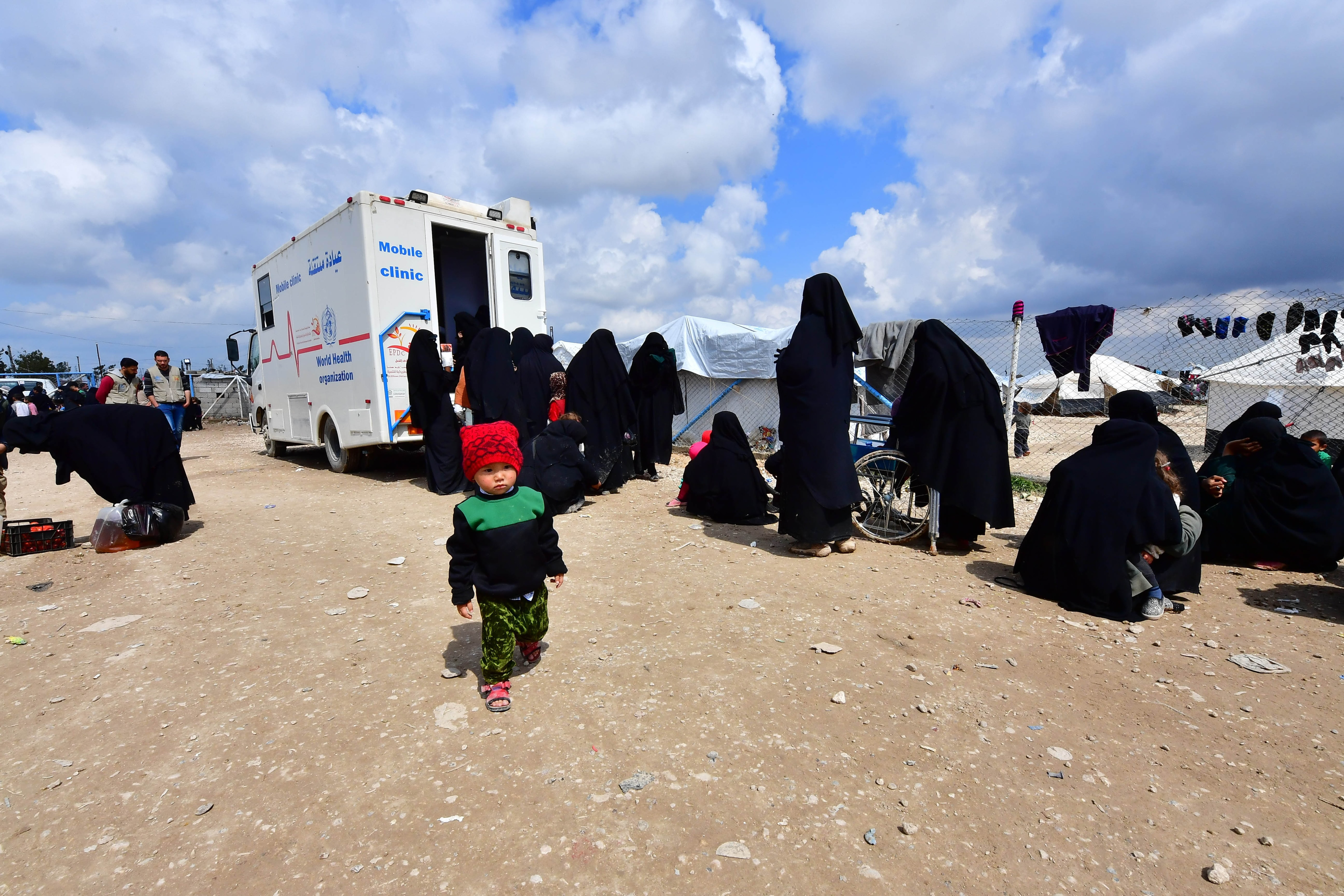 Veiled women living in al-Hol camp which houses relatives of Islamic State (IS) group members, queue to receive medical aid.
