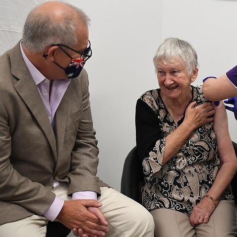 Prime Minister Scott Morrison joins Jane Malysiak (right) as she receives the first COVID-19 vaccine in Australia