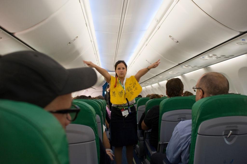 A flight attendant gives a safety demonstration