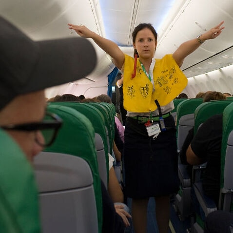 A flight attendant gives a safety demonstration
