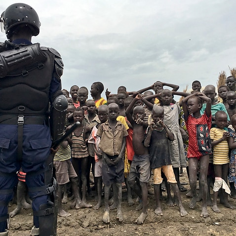 A crowd of displaced people in South Sudan look on as members of the U.N. multi-national police contingent provide security.