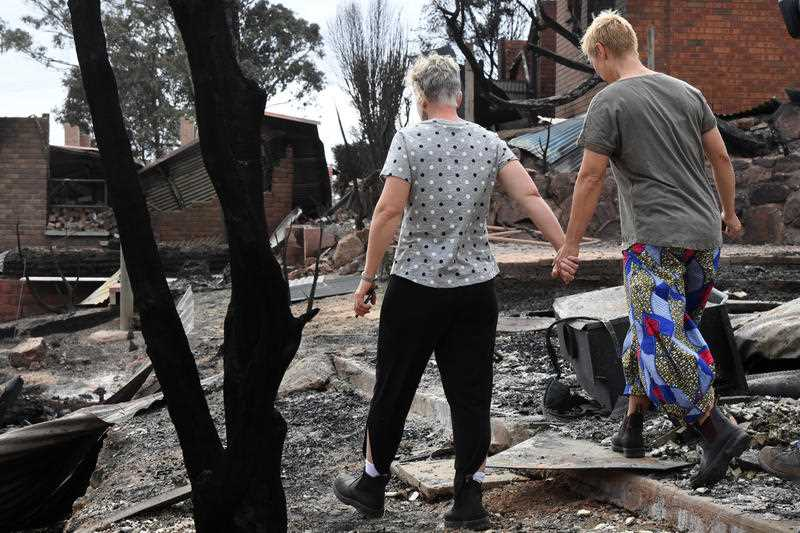 Tathra residents Ingrid Mitchell (right) and Deb Nave (left) wander through the burnt out remains of their Wildlife Drive home in Tathra.