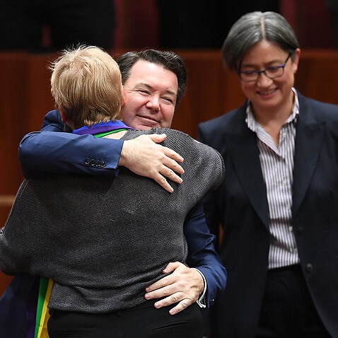 Australian Greens Senator Janet Rice (left) receives a hug from Liberal Senator Dean Smith after speaking on The Marriage Amendment Bill.