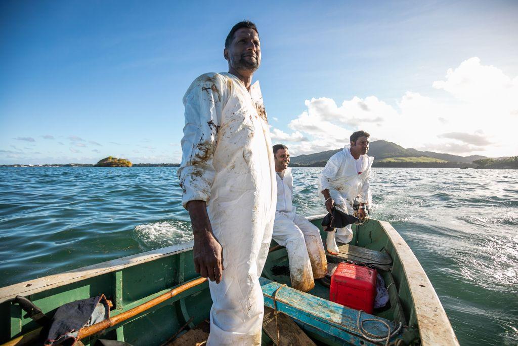 手作りのオイルバリアを海に配置しながら漁師が見守る