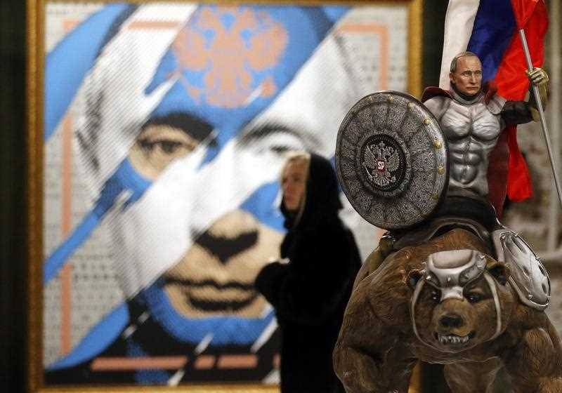 A visitor in front of an artwork depicting Russian President Vladimir Putin during the SUPERPUTIN exhibition at the Ultra Modern Art Museum (UMAM) in Moscow, Russia, 07 December 2017.