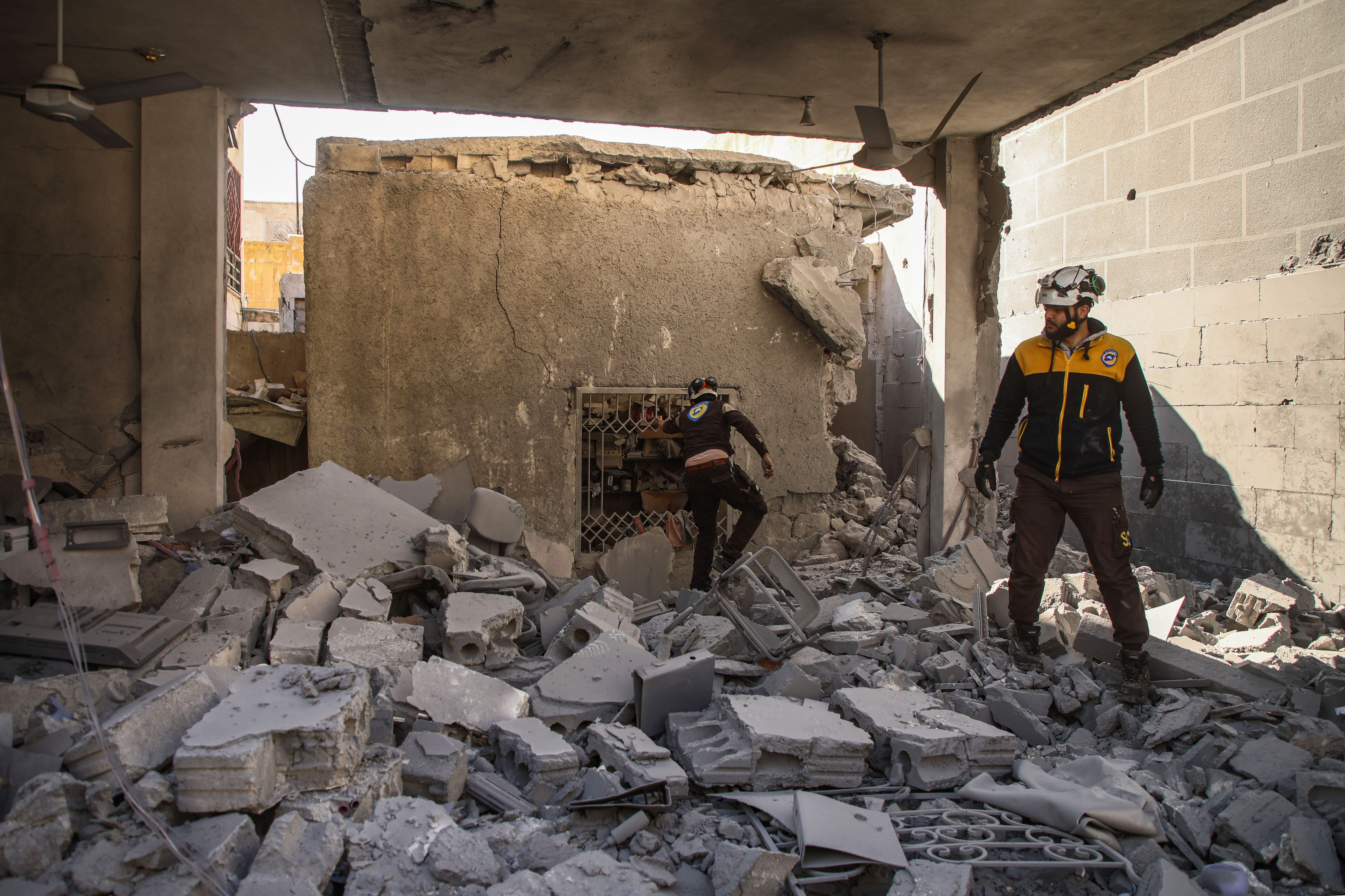 Members of the Syrian Civil Defence inspect debris and rubble as they search for survivors at a destroyed hospital in the town of Darret Ezza.