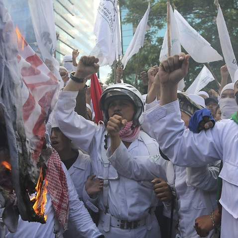 Members of the militant Islamic Defenders Front (FPI) burn a mock Australian and US flags during a demonstration outside Australian Embassy in Jakarta in 2013.