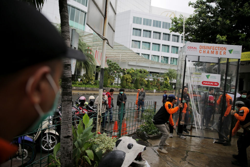 Indonesia people reacts as she is sprayed with disinfectant inside a makeshift sterilisation chamber