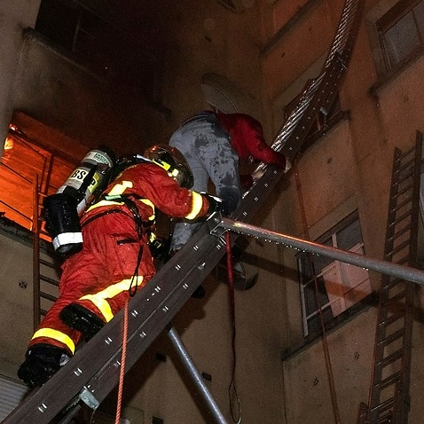 Firefighters rescue a woman from the burning building.