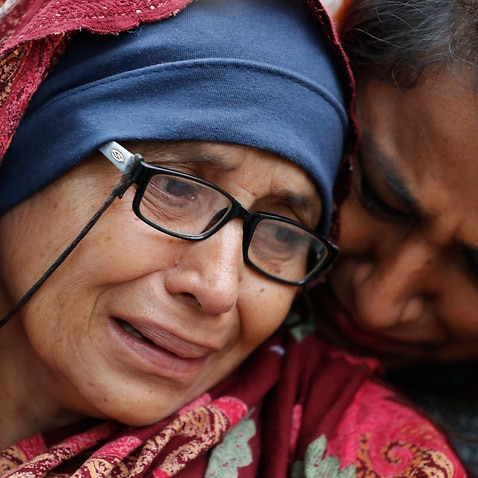 A women who lost her husband during cries outside a information center for family in Christchurch, New Zealand.