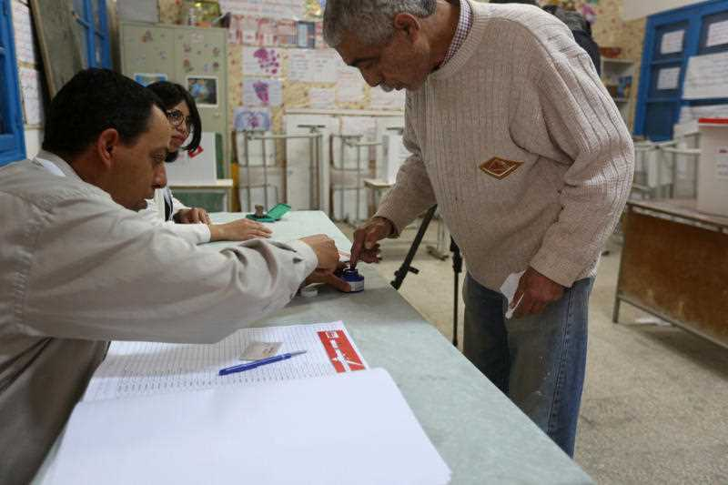 A Tunisian dips his finger in ink before casting his vote at a polling station in Ben Arous, near the Tunisian capital Tunis