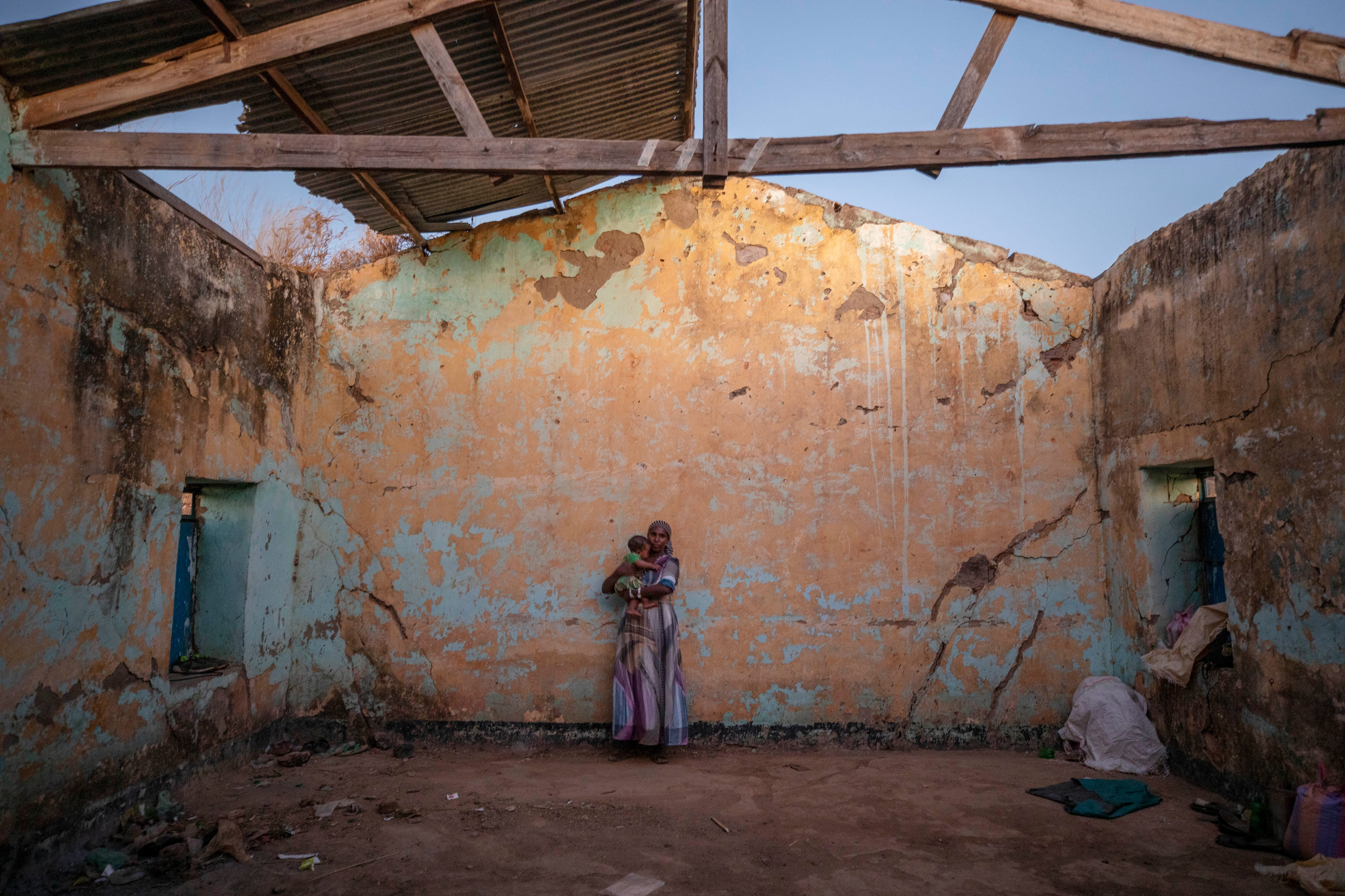 A woman who fled the conflict in Ethiopia's Tigray region holds her child inside a temporary shelter at Umm Rakouba refugee camp in Qadarif, Sudan.