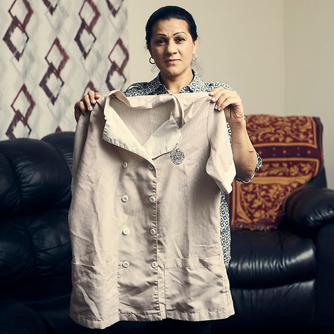 Sandra Diaz holds her housekeeping uniform from her time working at the Trump National Golf Club in Bedminster, N.J., at her home in Bound Brook, N.J.