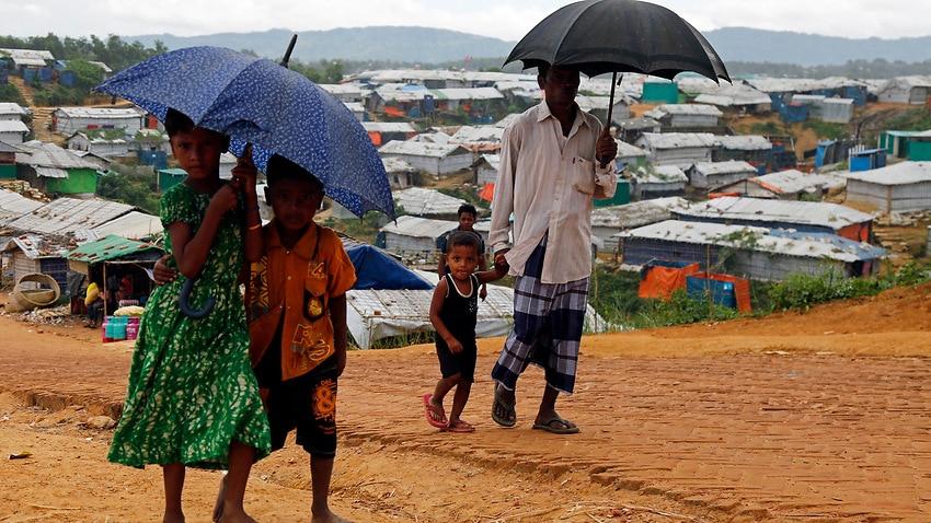 Rohingya refugees during the rain season walk on a road along a makeshift camp in Kutubpalang, Cox Bazar district.