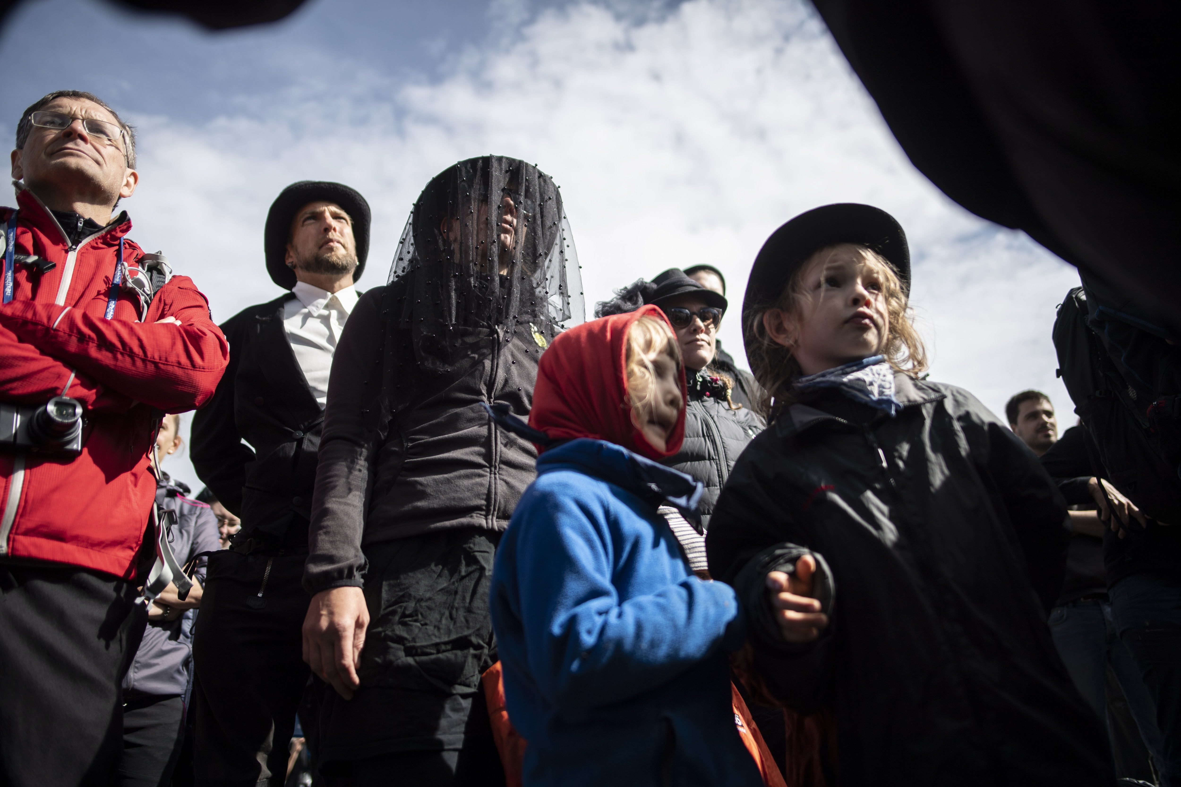 People in black clothing attend a commemoration for the dying glacier of Pizol mountain, in Wangs, Switzerland.