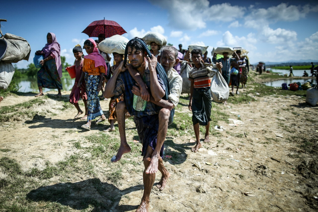 A Rohingya refugee who carries his father for the last 3 days is returned to the quarantine area after waiting hours at the Myanmar-Bangladesh border.