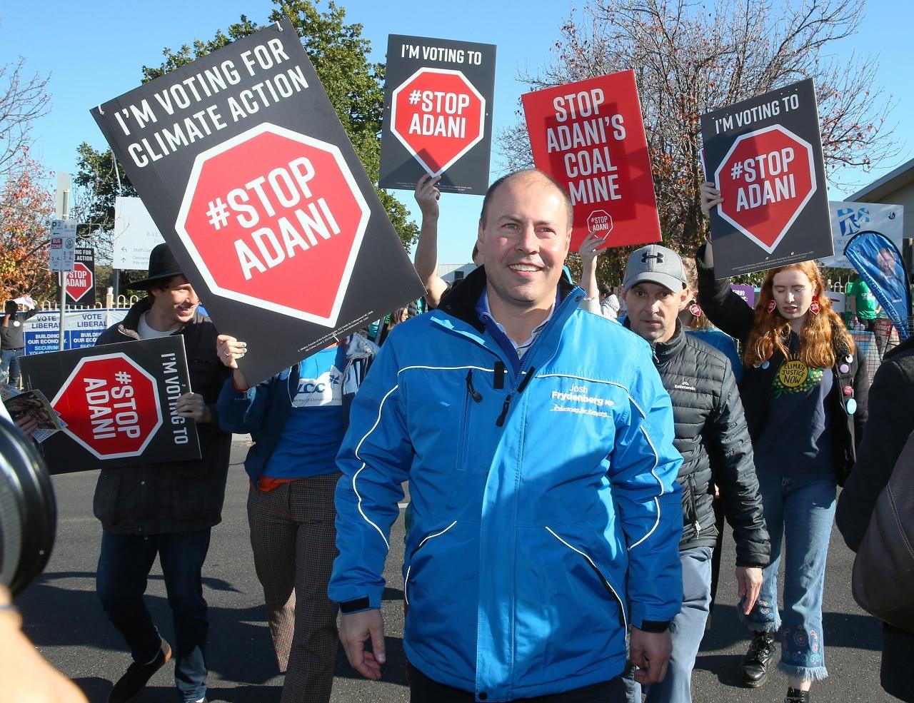 Treasurer Josh Frydenberg is followed by anti Adani protesters.