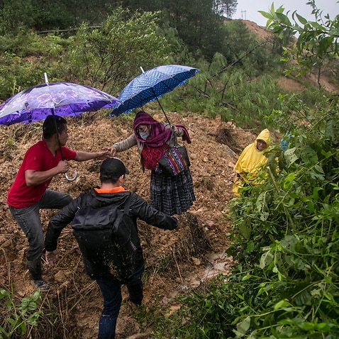 People make their path through a landslide caused by heavy rains brought by tropical depression Eta in Purulha, Baja Verapaz department, Guatemala.