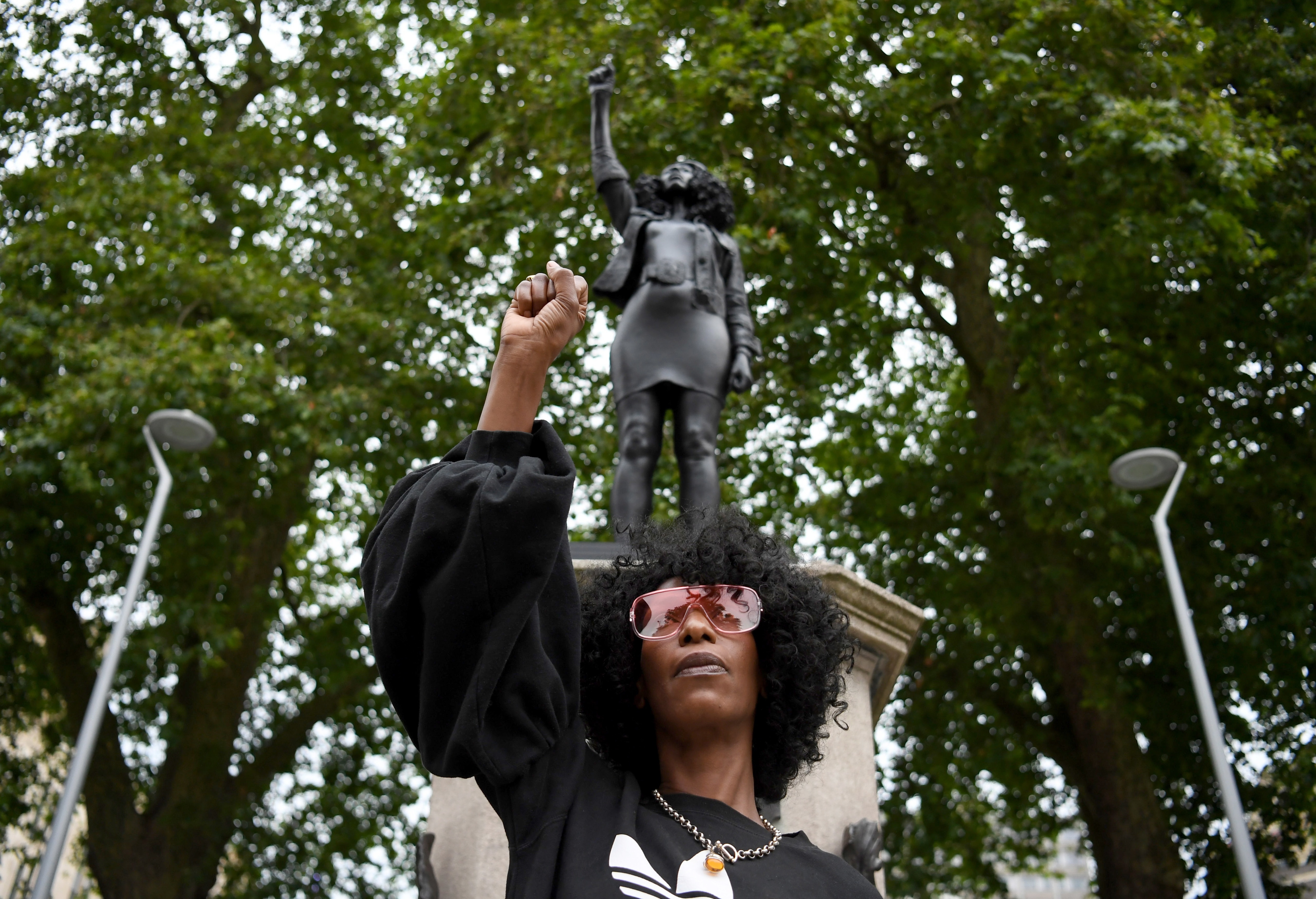 B;ack Lives Matter protester Jen Reid poses in front of a statue of herself.