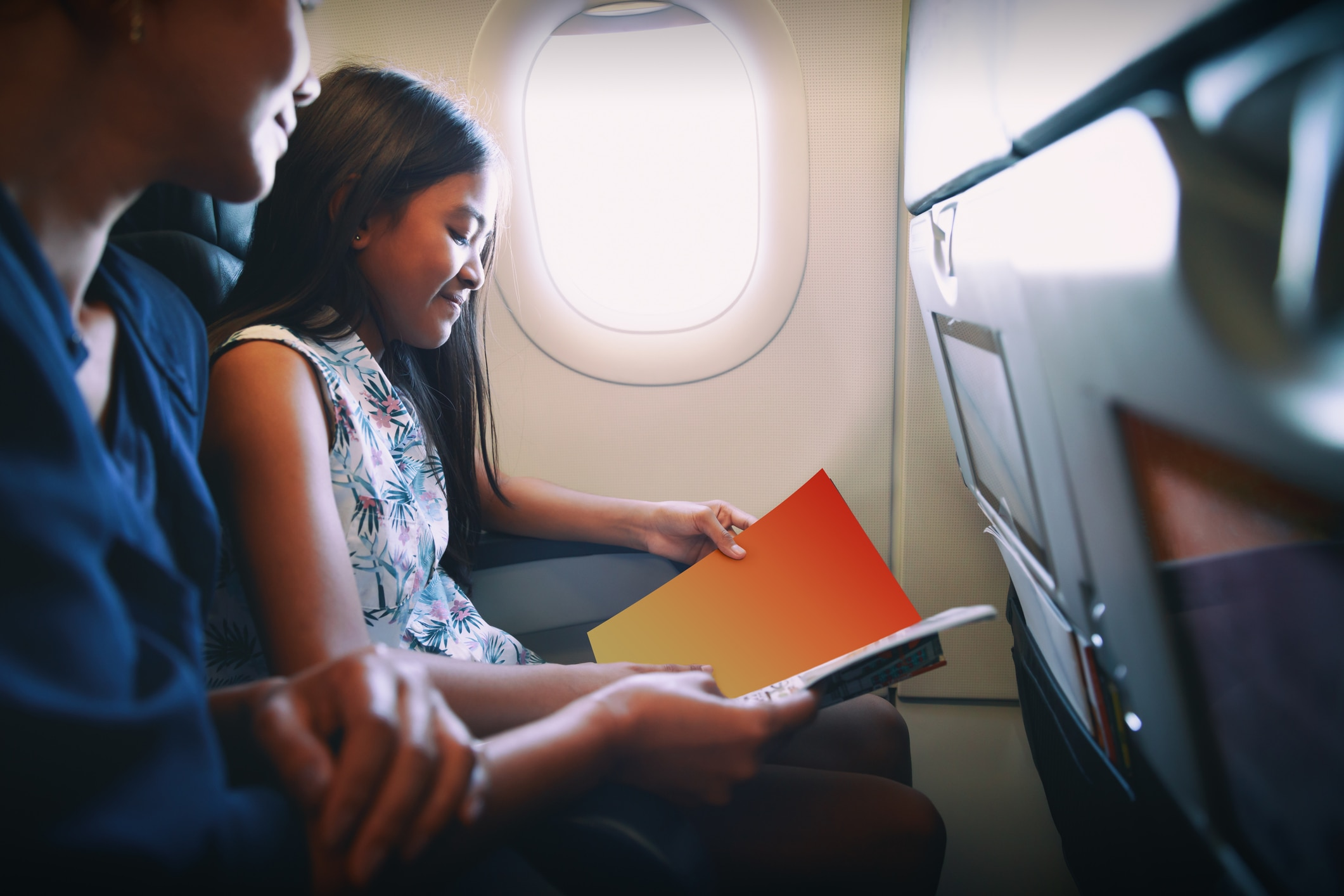 Mother with daughter sit on their place in airplane