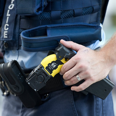 Stock photograph of a Queensland Police Officer with his hand on a taser