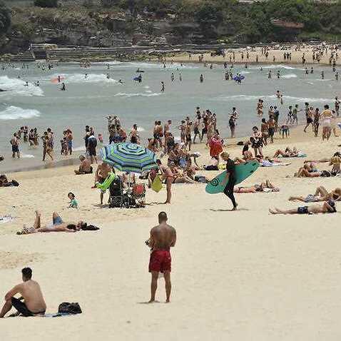 People gather on the sand at Bondi Beach in Sydney