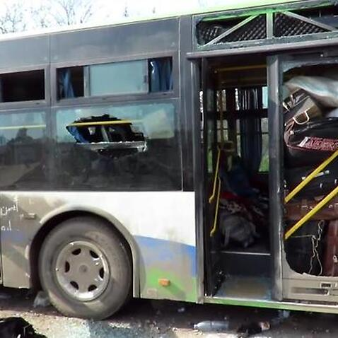 A handout photo made available by Thiqa News Agency (TNA) showing a damaged bus at the scene of a car bomb attack that targeted buses evacuating civilians (AAP)