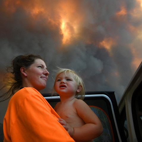 Sharnie Moren and her 18 months old daughter Charlotte look on as thick smoke rises from bushfires near Nana Glen, near Coffs Harbour, Tuesday, 12 November