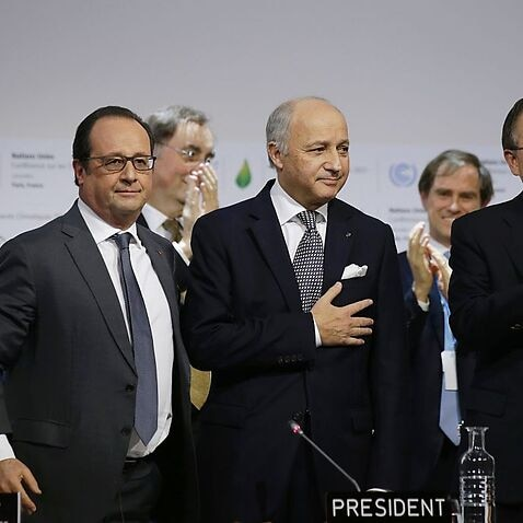 French Foreign Affairs Minister Laurent Fabius and President-designate of COP21 puts his hand over his heart after his speech as he stands with French President Francois Hollande, French Ecology Minister Segolene Royal and United Nations Secretary-General