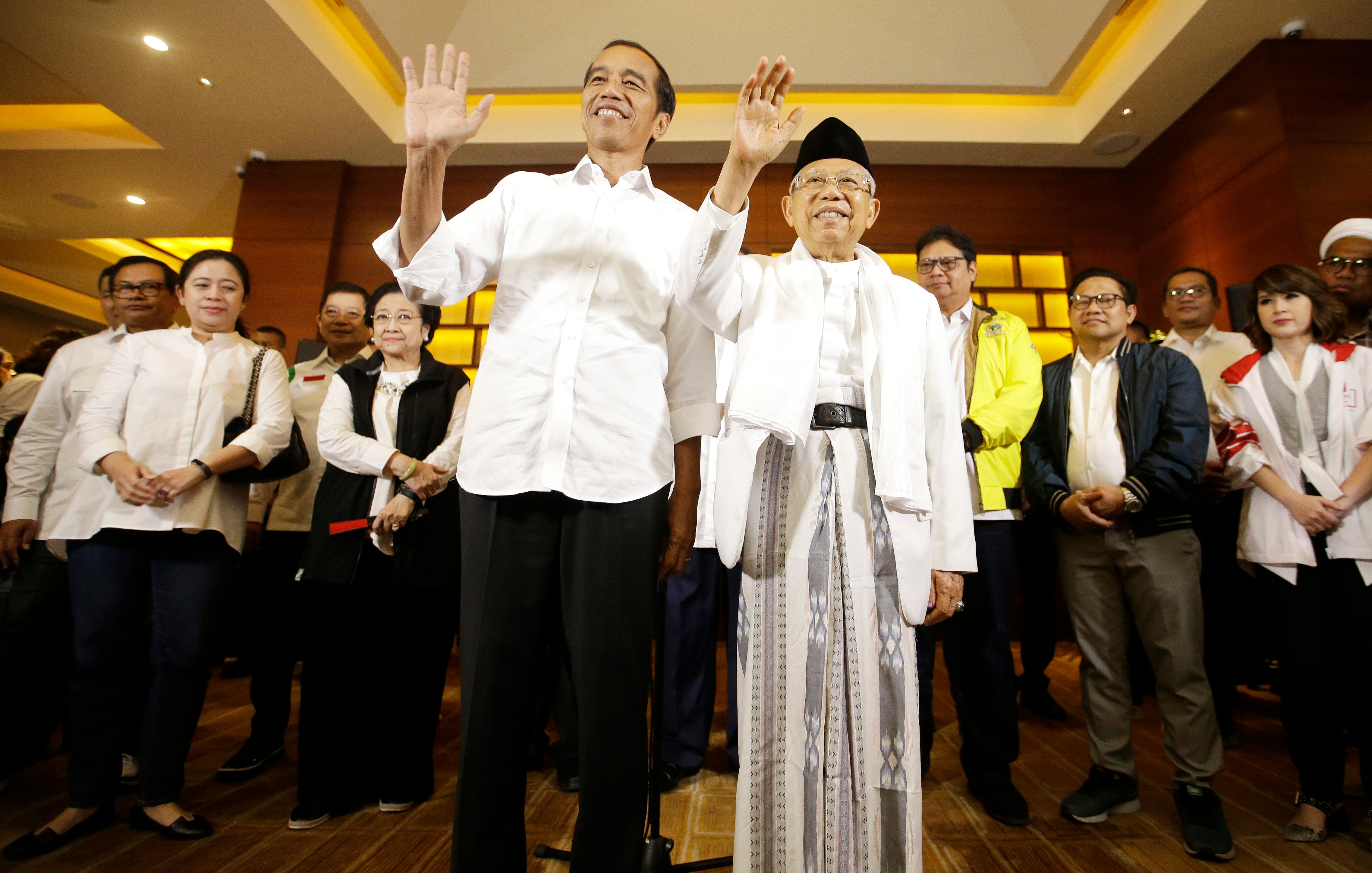 Indonesian President Joko Widodo and his running mate Ma'ruf Amin, right, wave to journalist  after a press conference in Jakarta, Indonesia.