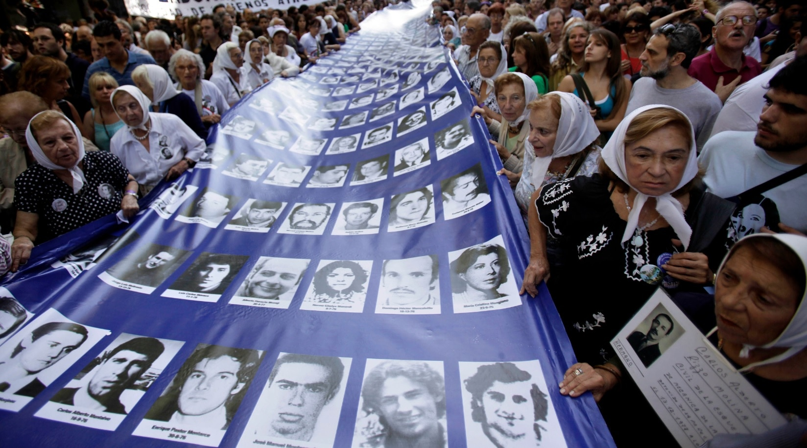 Members the Argentinian Grandmothers of the Plaza de Mayo and Mothers of the Plaza de Mayo, carrying a banner with images of people missing