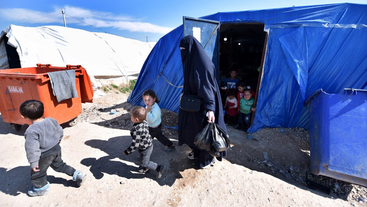 An unidentified woman, reportedly a wife of a suspected Islamic State (IS) fighter, walks with her children at Roj refugees camp in Hasakah, northeast of Syria.