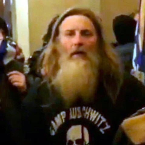 A man who was filmed wearing a 'Camp Auschwitz' shirt at the 6 January riots has been arrested.