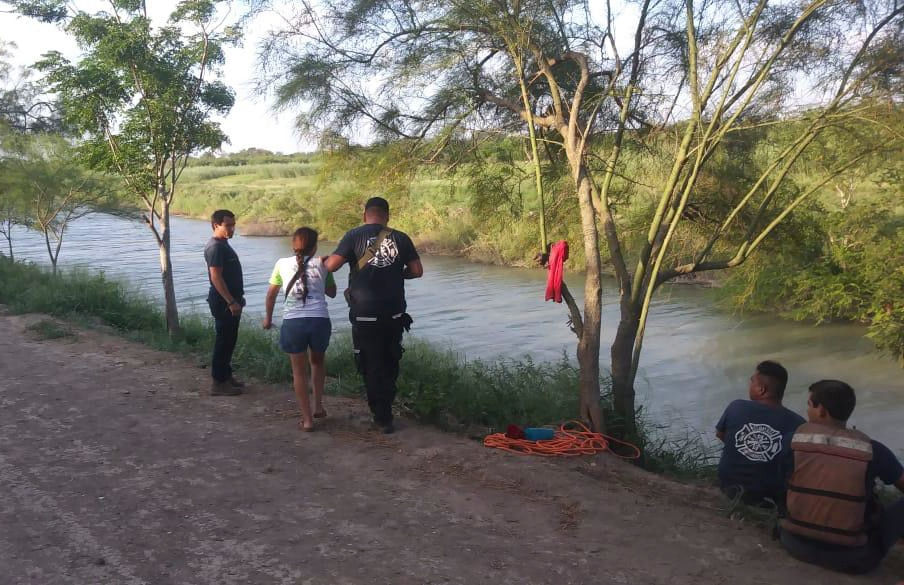 Tania Valos, center left, is assisted by Mexican authorities after her husband and two-year-old daughter were swept away while trying to cross the Rio Grande