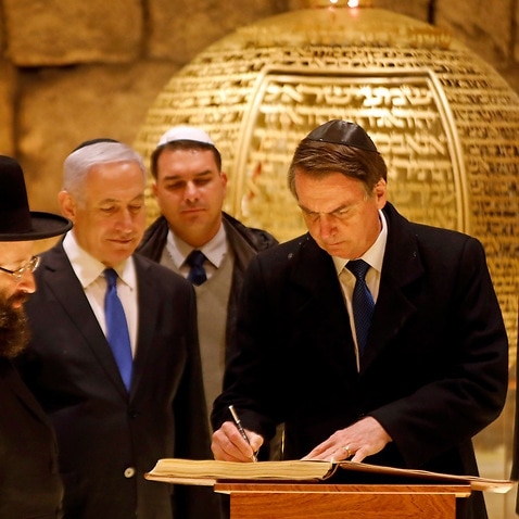 Brazilian President Jair Bolsonaro signs a book during a visit to a synagogue inside the Western Wall Tunnels in Jerusalem's Old City on 1 April, 2019.