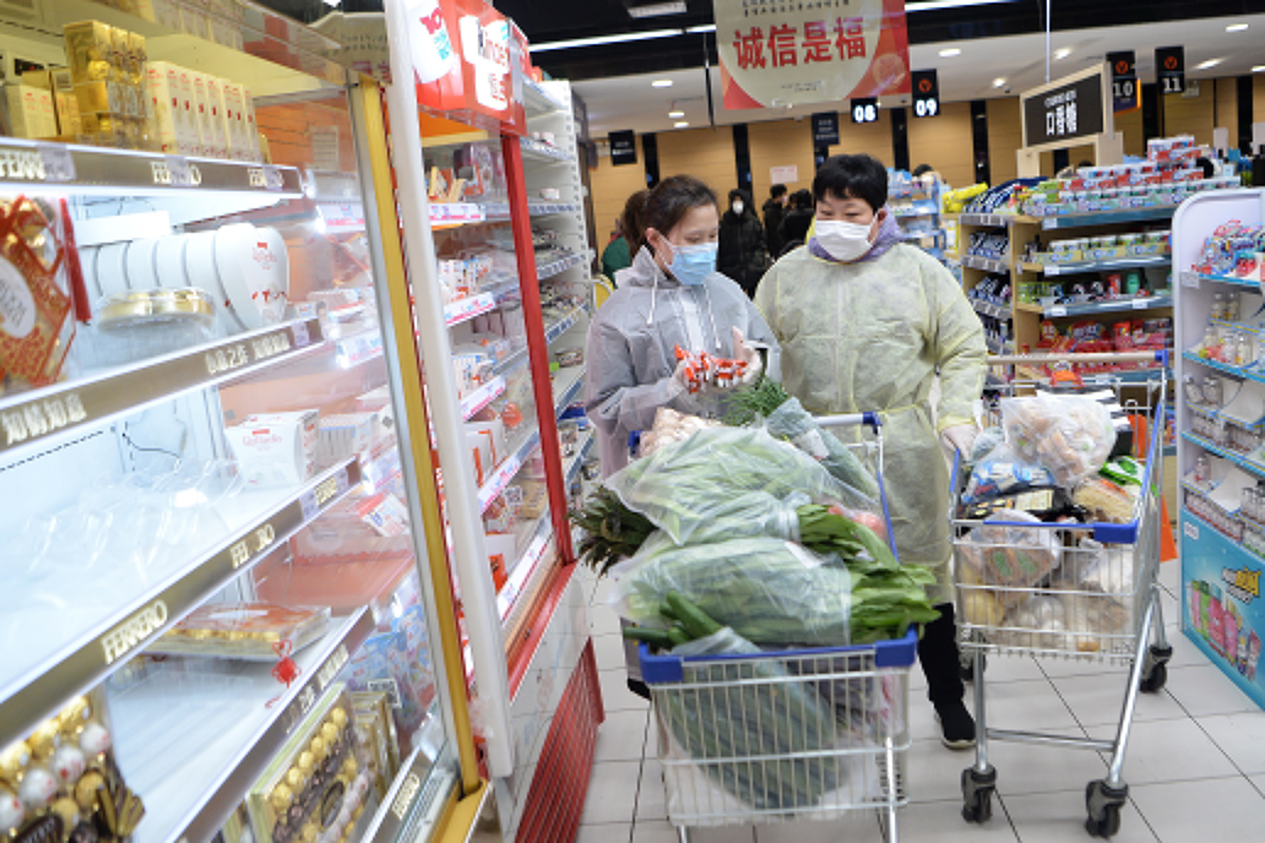 Masked shoppers wearing plastic coats shop in a supermarket in Wuhan, the epicenter of the coronavirus outbreak.
