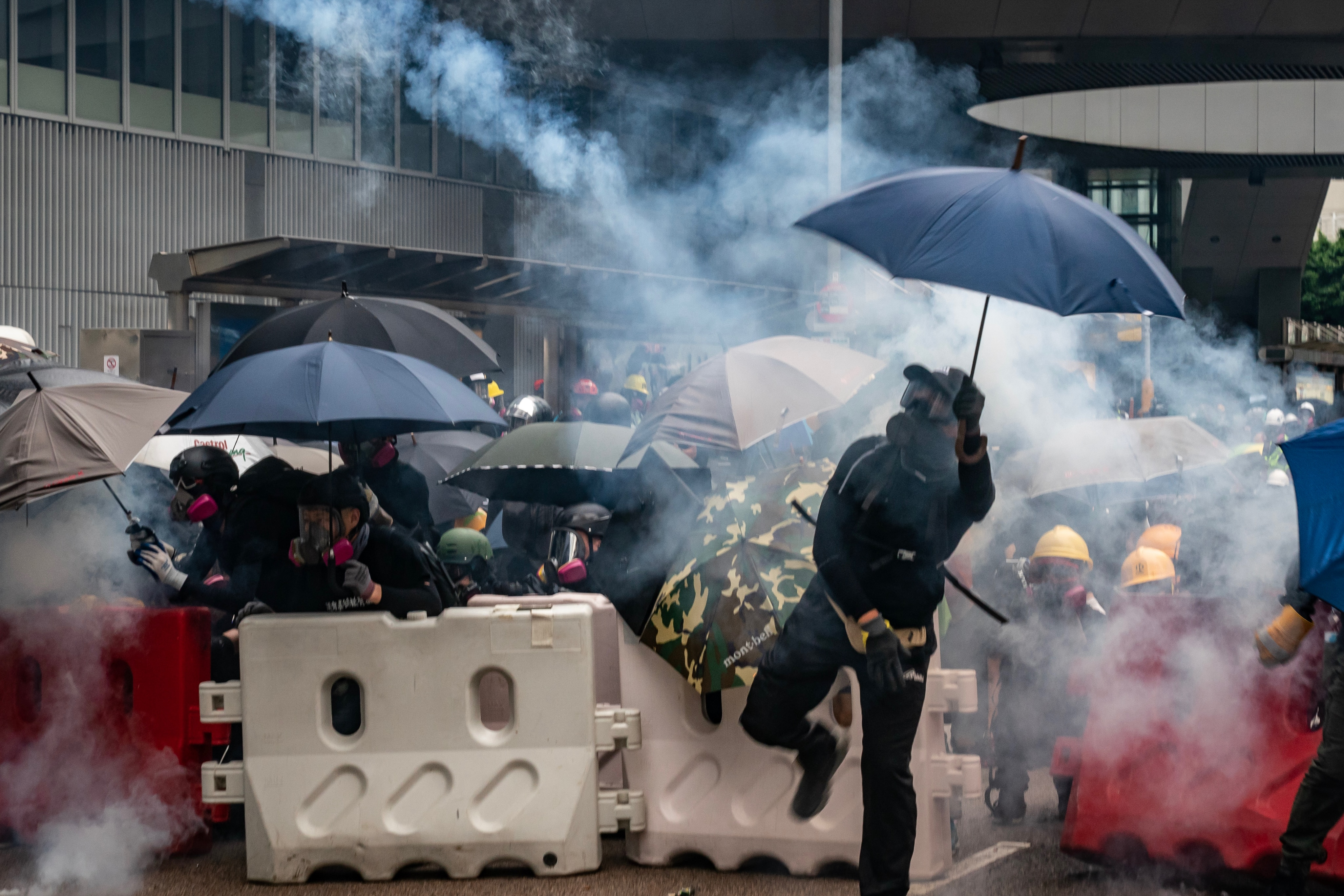 Protesters throw tear gas canisters back at police during an anti-government rally outside of Central Government Complex.